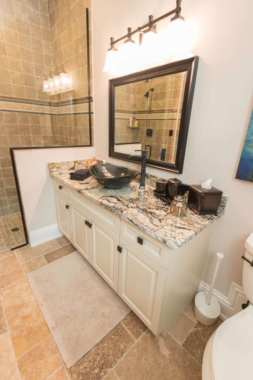 traiditonal antique white vanity cabinet with black and white granite counterts and black sink and faucet