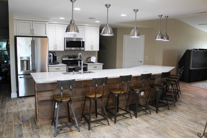 Industrial style kitchen with cream perimeter cabinets and reclaimed wood on the back of the island. Granite countertops throughout with stainless industrial fixtures.