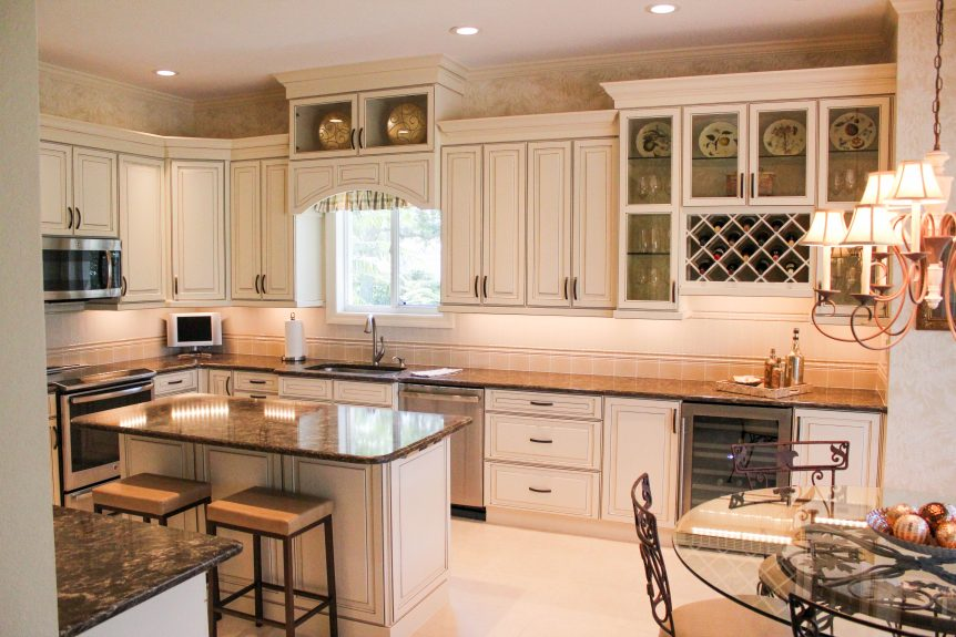 Luxury traditional kitchen with cream cabinets, black glaze, and brown granite countertops.