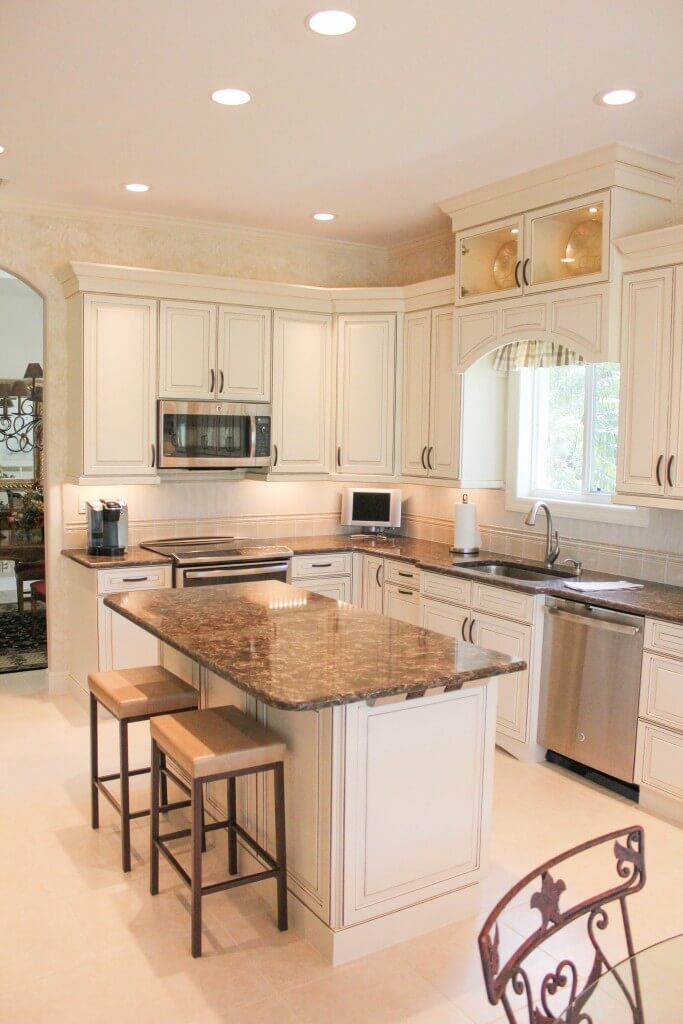 Nicely sized traditional kitchen with antique white paint and brown glaze with brown quartz countertops