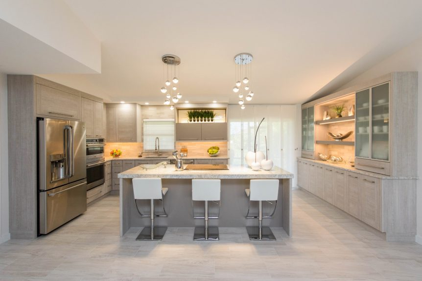 Ultra modern kitchen with grey textured cabinetry, glass doors, matte grey accents, stainless appliances, quartz countertops, featuring a large island.