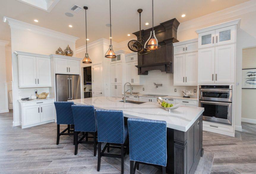 Absolutely elegant kitchen with slate grey island and two-tiered hood vent, white shaker perimeter cabinets, white quartz countertops, and stainless appliances.