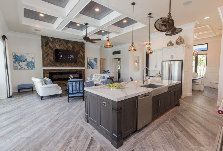 Stunningly elegant kitchen with slate grey island, white shake perimter cabinets, stainless farm sink, and white quartz countertops, and reclaimed wood floors.