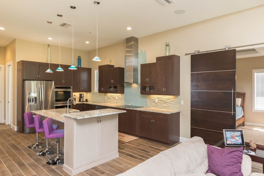 Contemporary kitchen with dark brown perimeter cabinets, pickled island cabinets, and granite countertops. Kitchen features a glass cooktop backsplash running up the wall.