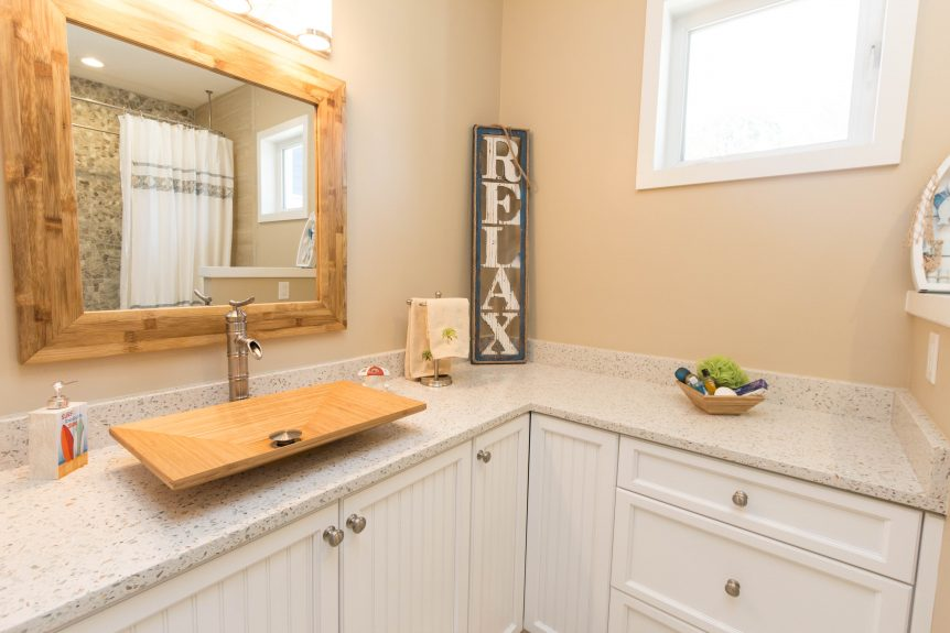 white bead board vanity with bamboo sink bowl and brushed nickel faucet